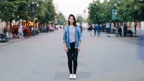 Time-schackningsperiod stående av den stressade unga kvinnan som bara står i bärande jeans för centrum och grov bomullstvillomsla lager videofilmer
