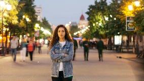 Time-schackningsperiod stående av det ensamma anseendet för ung dam i gatan som är i stadens centrum med korsade armar, medan fol lager videofilmer
