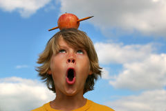 Time for School. Boy surprized by pencil shooting through apple on his head. (metaphor for back to school Stock Photography