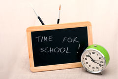 Time for school blackboard and old table clock Stock Images