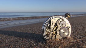 Time and sea concept - vintage clock on sea beach. Time and sea concept - analog pocket vintage clock on wet sea beach sand stock video