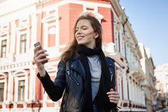 Time for selfie. Outdoor shot of attractive businesswoman on trip with company teammates, walking around city while. Having spare time, holding smartphone Royalty Free Stock Photography