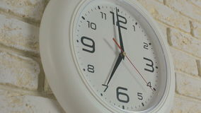 Time seven hour. Timelapse. Round white clock hanging on brick wall. stock video footage