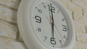 Time six hour. Timelapse. Round white clock hanging on brick wall. Time six hour. Timelapse. Round white clock hanging on a brick wall stock video