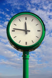 Time in the sky. Green street clock against sky Stock Images