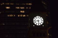 Time sneaks in the dark even if you don t notice. Toronto old city hall clock tower before the skyscraper in the night.  Royalty Free Stock Photos