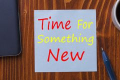 Time For Something New. Written in note with pen, smartphone and cup of coffee on wooden desk top view Royalty Free Stock Image
