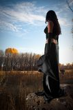 It is time for sorcery. Pretty witch standing on stone among field Stock Photo