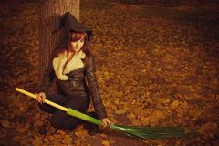 It is time for sorcery. Pretty young with with broom sitting in the autumn forest Royalty Free Stock Images