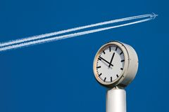 Time and Speed. City clock in the foreground. Flying airplane in the background Stock Photography