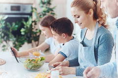 Family members reuniting at kitchen island. Time spent with family is worth every second. Side view on parents making vegetable salad while their kids sitting Stock Photography