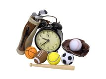 Time for sports. Various sports equipment scattered around an old fashion alarm clock - path included Royalty Free Stock Photos