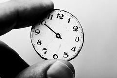 Time stands still. Black and white picture of two fingers holding a clock dial Royalty Free Stock Photo