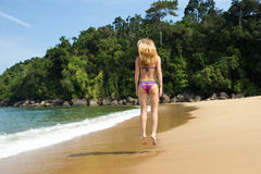 Time stood still. Blond woman from the back jumping on a beach being in a harmony and enjoing her vacation Royalty Free Stock Photography