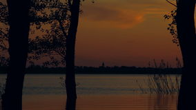 Time of sunset on the lake. In the distance can be seen the silhouette of the church on the sunset sky background stock video footage
