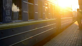 At the time of sunset train with blue wagons leaving from the train station stock footage