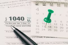 Time for tax in April concept, green pin on day 17 of April calendar with pen on 1040 US individual income tax filling form royalty free stock images