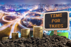 Time for Taxes - Financial opportunity concept. Golden coins in soil Chalkboard on blurred urban background Royalty Free Stock Photos