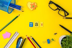 Time for Taxes. Money Financial Accounting. Taxation Concept with office suplies at yellow background.  Royalty Free Stock Photos