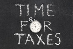 Time for taxes. Phrase handwritten on chalkboard with vintage precise stopwatch used instead of O Stock Photography