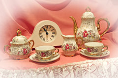 Time for tea!. Photo of a country tea shop window display, showing a beautiful vintage ornate tea set and clock set at eleven..that can only mean one thing..time Royalty Free Stock Images