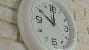 Time ten hours. Timelapse. Round white clock hanging on brick wall. Time ten hours. Timelapse. Round white clock hanging on a brick wall stock footage