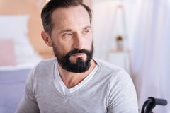 Serious disabled man of middle age thinking. Time for thoughts. Serious bearded dark-haired handicapped man looking in the distance and thinking and wearing a Royalty Free Stock Photo