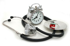 Time to accept tablets. Tablets, a stethoscope and an alarm clock isolated on a white background Stock Image