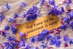 The time to be awesome is now. In looking memo on white wood with beautiful blue flowers around royalty free stock photos