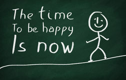 The time to be happy is now. On the blackboard draw character and write The time to be happy is now Stock Photo