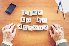Time to be strong. Businessman made text from wooden cubes stock images