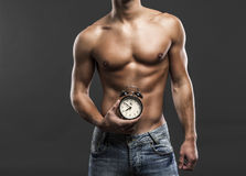 Time to be strong. Sexy and handsome young man holding a clock over his belly Royalty Free Stock Images