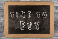 Time to buy - chalkboard with outlined text. On wood Stock Photo