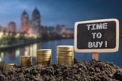 Time to buy - Financial opportunity concept. Golden coins in soil Chalkboard on blurred urban background Royalty Free Stock Image