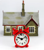 Time to Buy That House. A red Alarm clock in front of a house, asking the question is it time to sell or buy stock photos