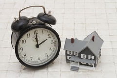 Time to buy a house, A gray house and alarm clock on stone backg Royalty Free Stock Photos