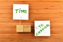Time to change, two paper notes with holders on wood Royalty Free Stock Image