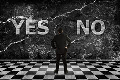 Time to choose. Businessman trying to choose between a yes or no option stock image