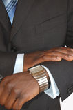 Time to close the deal. This is an image of a black business man checking the time Royalty Free Stock Photography