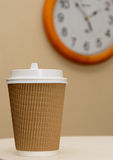 Time to coffee break. Coffee in brown paper cup on the clock background Stock Photos
