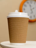 Time to coffee break. Coffee in brown paper cup on the clock background Royalty Free Stock Photos