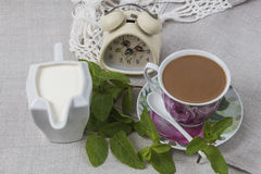 It is time to coffee break. Cup of coffee on a saucer with a spoon, a jar of cream and an alarm clock on gray linen table cloth, decorated with green mint Royalty Free Stock Photography
