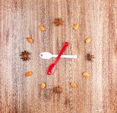 Time to cook. Clock face on a wooden background of almonds and star anise with arrow of measuring spoons Stock Photo