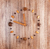 Time to cook. Clock face on a wooden background of almonds and coffee beans with arrow of cinnamon sticks Stock Photography