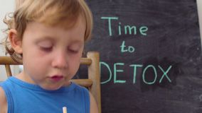 TIME TO DETOX chalk inscription. The boy is drinking fresh, healthy, detox drink made from fruits. Fruit shake, fresh juice, milks stock video