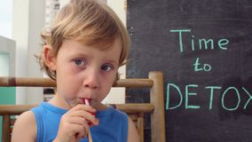 TIME TO DETOX chalk inscription. The boy is drinking fresh, healthy, detox drink made from fruits. Fruit shake, fresh juice, milks stock footage