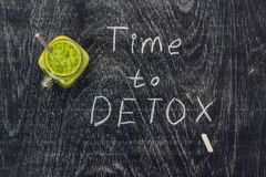 TIME TO DETOX Chalk Inscription On The Wooden Table And Green Smoothies Made Of Spinach. Healthy Eating And Sports Concept Stock Photo