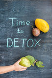 TIME TO DETOX chalk inscription on the wooden table fruits: mango, passion fruit and guava. Hand stretching to guava. Health Conce Royalty Free Stock Photography