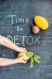 TIME TO DETOX chalk inscription on the wooden table fruits: mango, passion fruit and guava. Hand stretching to guava. Health Conce Stock Photography