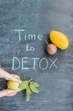 TIME TO DETOX chalk inscription on the wooden table fruits: mango, passion fruit and guava. Hand stretching to guava. Health Conce Royalty Free Stock Photo